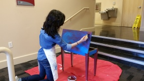 Lady kneeling on a red sheet while painting a on a table.