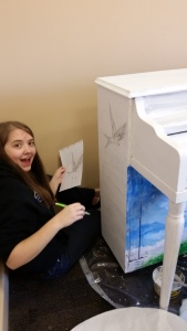 A girl that is drawing on the side of a white piano.