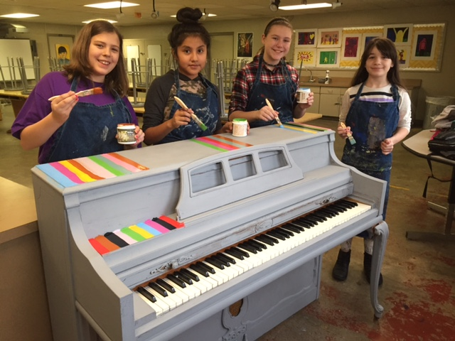 Four girls posing with paint brushes while in the middle of painting the top of a piano.