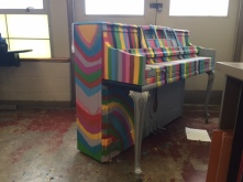 A piano that has been painted colorfully.