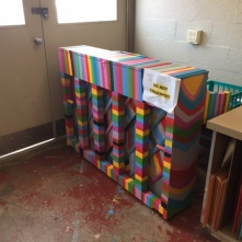 """Rainbow colored piano sitting next to two doors with a """"Do Not Touch!"""" sign on it."""