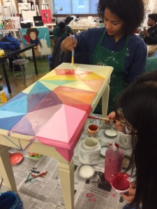 A girl painting a design on a table top.