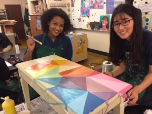Two girls smiling while painting the top of a table.