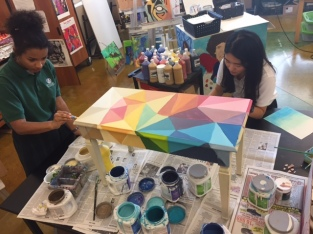 Two girls painting rainbow colors unto a table.