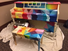 A sitting piano painted in orange, yellow, red, purple, pink, and different variations of blue.