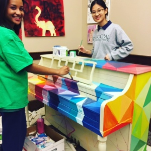 Two girls standing and painting rainbow colors unto a piano.