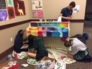 Three girls sitting and one guy standing painting rainbow colors unto a piano.