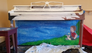 A piano with a picture of a boy sitting in grass on it.