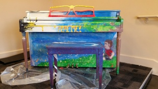 A colorful piano that was is in the process of being painted.